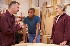 Timmerman Talking To Apprentices in Timmerwerkworkshop stock foto