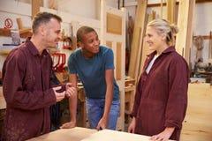 Timmerman Talking To Apprentices in Timmerwerkworkshop royalty-vrije stock fotografie