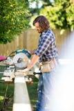 Timmerman Using Table Saw om te snijden Houten Plank bij royalty-vrije stock afbeeldingen