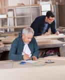 Timmerman Working On Blueprint op Workshop Stock Fotografie