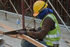 Timmermans zagend hout bij de bouwwerf Stock Afbeelding