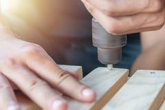 Timmermansboor een houten raad met een elektrische boor Royalty-vrije Stock Afbeelding