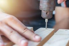 Timmermansboor een houten raad met een elektrische boor Royalty-vrije Stock Afbeeldingen