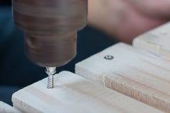 Timmermansboor een houten raad met een elektrische dril Royalty-vrije Stock Afbeeldingen