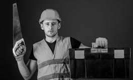 Timmermansconcept De mens in helm, bouwvakker draagt toolbox en houdt handsaw, blauwe achtergrond Arbeider, hersteller royalty-vrije stock afbeeldingen