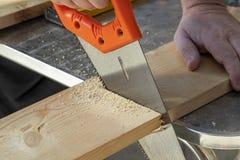 Timmermanshand met handsaw die houten raad snijdt Timmerwerk, bouw royalty-vrije stock afbeeldingen