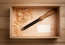 Timmermanshulpmiddelen in houten doos en adreskaartje Royalty-vrije Stock Fotografie