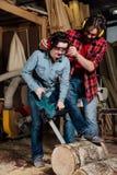 Timmermansvrouw en man met elektrische kettingzaag in workshop stock afbeelding