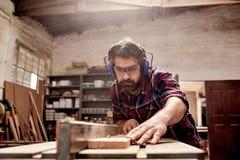 Timmerwerk bedrijfseigenaar die een plank van hout in workshop snijden stock afbeeldingen