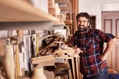 Timmerwerk bedrijfseigenaar status die in zijn workshop glimlachen stock afbeeldingen
