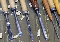 Timmerwerkhulpmiddelen voor houtsnijwerk op de lijst met zaagsel stock afbeelding