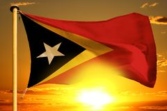 Timor-Leste flag weaving on the beautiful orange sunset with clouds background. Timor-Leste flag weaving on the beautiful orange sunset background royalty free stock photo
