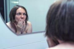 Timore di ottenere vecchio, femmina adulta davanti allo specchio immagini stock