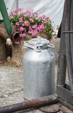 Big can for fresh milk. Tin bin once used with a composition of pink geraniums behind royalty free stock photo