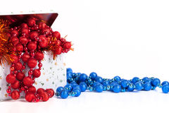 Tin box with blue and red beads and tinsel on a white background Stock Photos