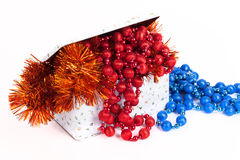 Tin box with blue and red beads and tinsel on a white background Stock Images