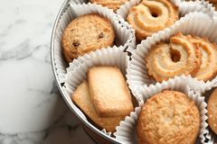 Tin box with Danish butter cookies on marble table, closeup. Space for text stock photos
