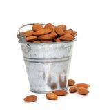 Tin bucket full of almonds on white background Stock Photos