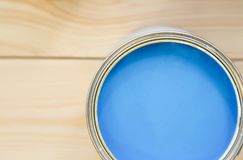 A tin can of blue paint. Painting an appartment. A tin can of blue oil paint on a light uncolored wooden background. Close up. Top view. Space for your text or Royalty Free Stock Image