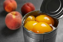 Tin can with conserved peach halves. On table, closeup stock photo