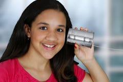Tin Can Phone. Teen girl listening to a tin can phone Royalty Free Stock Photos