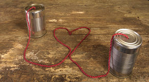 Tin can phone with heart shape in wire Stock Photo