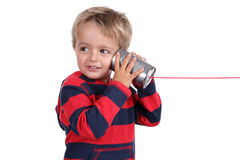 Tin can phone. Little boy listening through a tin can phone connected by string, concept for communication Stock Photo