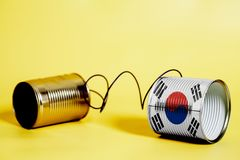 Tin can phone with South Korea Flag.communication concept. On yellow royalty free stock photos