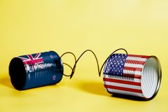 Tin can phone with USA and New Zealand Flag.communication concept. On yellow royalty free stock images