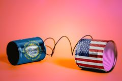 Tin can phone with USA and South Dakota USA State Flags. communication concept royalty free stock photos