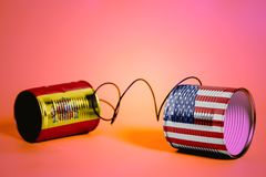 Tin can phone with USA and Spain Flags.communication concept royalty free stock images