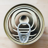 Tin can with ring pull from above. Tin can (canned food) with ring pull directly from above on wooden table stock photography