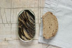 Tin can of sprats, sardines with bread pieces on wooden table. Top view and free space. stock photos