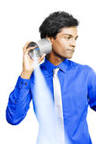 Tin can telephone communication. Young Asian business man listens carefully to an old-fashioned tin can telephone which transmits sound by vibration as he mulls Royalty Free Stock Image
