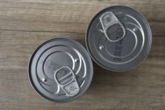 Tin cans for food on wooden background royalty free stock photography