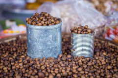 Tin cans and heap of roasted Lithocarpus seeds Stock Photo