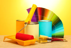 Tin cans with paint, rolle. R, brushes and bright palette of colors on wooden table on yellow background Royalty Free Stock Photo