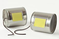 Tin cans phone with broken string and paper note - Communication stock images
