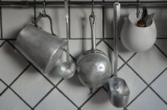 Tin coocking utensils hanging in kitchen Royalty Free Stock Photo