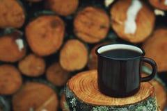 Tin cup of coffee. Tin mug with coffee. Tree stumps as background Stock Image