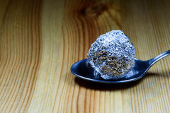 Tin Foil Heroin Lump on Silver Spoon. Ball of heroin wrapped in a tin foil ball resting on a silver teaspoon on a wooden textured surface Royalty Free Stock Photos