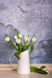 A tin jug filled with white tulips Stock Photography