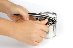 Tin opener. Woman's hand opening tin can with tin opener Stock Photo