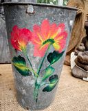 Tin Pail with Painted Flowers and Leaves. An old fashioned tin pail with red and yellow painted flowers and green leaves royalty free stock photos