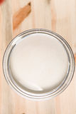 Tin of paint. Tin of silver paint on wooden surface Royalty Free Stock Images