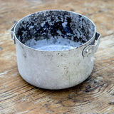 Tin pot. Old tin pot on old wooden table, close up Stock Images