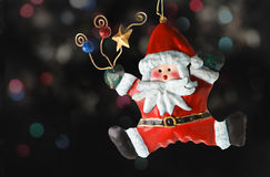 Tin Santa Claus. Christmas tree ornaments, with a background of blurry lights royalty free stock photography