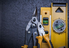 Tin snips gripping tongs construction level on. Black background Royalty Free Stock Image