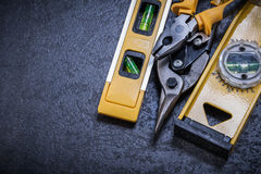 Tin snips pliers construction level on black Royalty Free Stock Photos