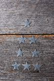 Tin Star Ornaments arranged in the shape of a Christmas Tree. On a rustic wood surface Royalty Free Stock Images